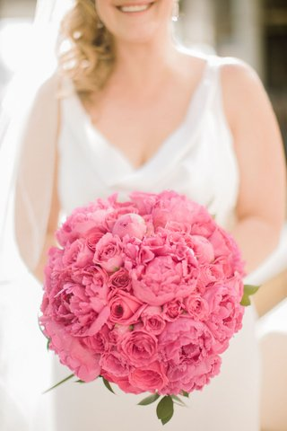 blonde-bride-holding-round-arrangement-of-peonies-and-roses