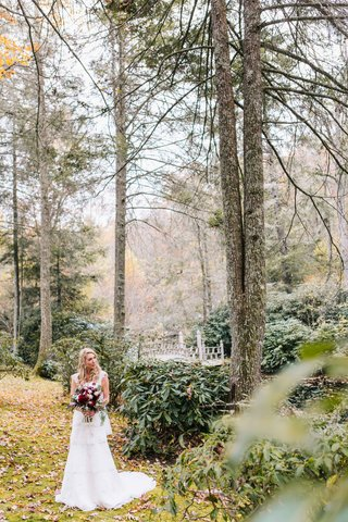 bride-with-wine-colored-floral-bouquet-and-white-dress-stands-in-field-and-forest-setting