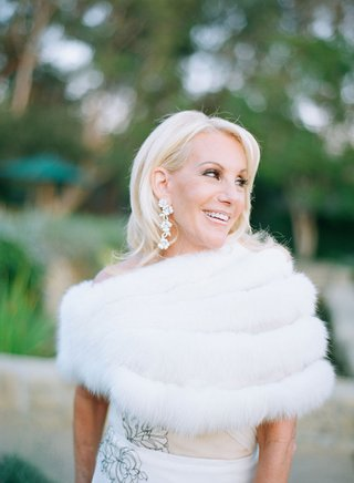 mother-of-bride-in-j-mendel-dress-with-white-fur-stole-and-flower-motif-earrings