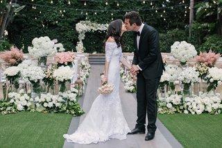 bride-in-lace-marchesa-wedding-dress-kissing-tuxedo-groom-in-front-of-garden-wedding-ceremony-decor