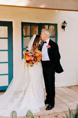 bride in lace wedding dress and veil with colorful bouquet father of bride kiss at la quinta resort and spa