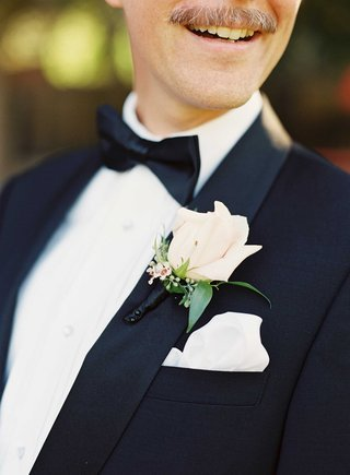 white-and-ivory-rose-bud-boutonniere-with-green-leaves-wrapped-in-black-ribbon-for-tuxedo-groomsman