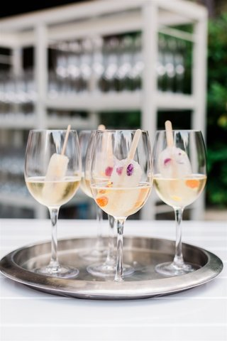 wedding ideas glass of champagne or prosecco with popsicle inside edible flowers