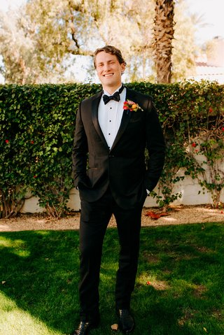 wedding photo of groom in tuxedo outside la quinta resort wedding colorful boutonniere