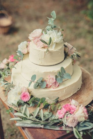three-layer-wedding-cake-ivory-frosting-decorated-with-greenery-pink-white-flowers-on-wood-stand