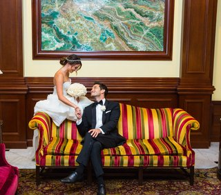 bride-and-groom-on-colorful-striped-couch-at-four-seasons-westlake-village
