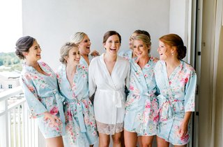 bride-in-white-lace-trim-silk-robe-with-bridesmaids-in-matching-light-blue-pink-robe-flower-print