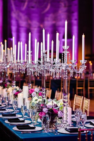 wedding reception long rectangular table with blue linen gold chairs crystal candelabra purple flowers