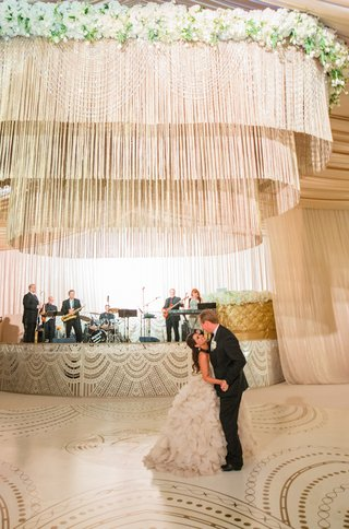 bride-in-ruffle-wedding-dress-dances-on-white-and-gold-dance-floor