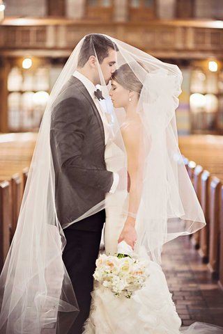 bride-and-groom-embrace-under-brides-veil-groom-kisses-forehead-in-chicago-church