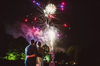 bride-and-groom-hug-while-watching-firework-show-purple-pink-fireworks-reception-ideas-entertainment