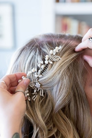 bride-with-lightly-curled-blonde-hair-hairstylist-putting-in-comb-pearl-rhinestone-crystal-details