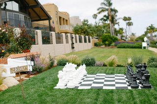 waterfront-wedding-with-large-black-and-white-chess-set-on-green-lawn