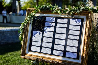 seating-chart-in-gold-frame-gold-calligraphy-find-your-seat-bulletin-board-garland-of-greenery