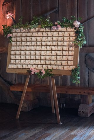escort-card-display-on-easel-with-greenery-escort-card-with-pink-floral-details