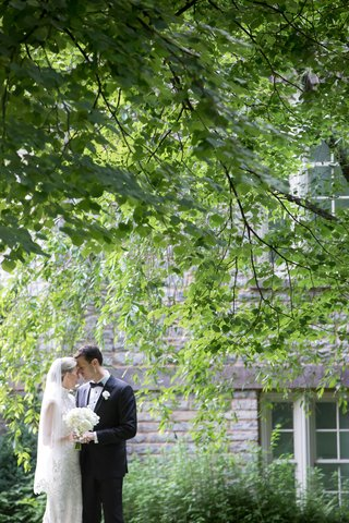 wedding-portrait-under-green-tree-in-front-of-historic-building-bride-in-veil-high-neck-lace-dress