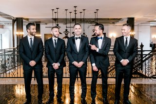 groom-in-tuxedo-groomsmen-in-suits-and-ties-and-best-man-in-tux-and-navy-blue-bow-tie
