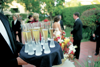 trumpet-shape-champagne-glasses-on-tray-with-formal-waiter