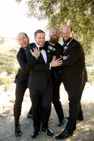 funny-groomsmen-picture-groom-and-groomsmen-in-tuxedos-playfully-pose