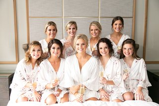 wedding portrait of bride in white robe with bridesmaids in flower print white robes holding flutes