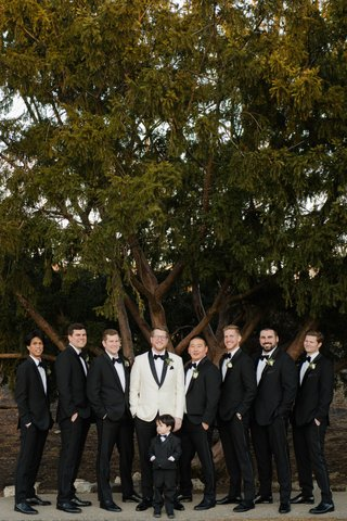 wedding-portrait-groom-in-white-tuxedo-jacket-groomsmen-in-black-white-tuxedo-suits-ring-bearer