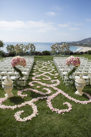 grass-lawn-ceremony-with-pink-flower-petals-and-white-chairs
