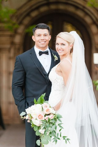 bride-in-lace-dress-martina-liana-holding-garden-bouquet-of-flowers-and-greenery-groom-in-tuxedo-bow