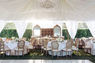 white-draped-tent-with-chandelier-and-rustic-upholstered-chairs