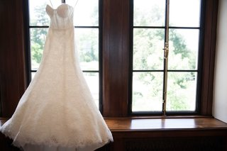 a-brides-gorgeous-gown-with-a-modified-a-line-skirt-and-corset-top-hung-up