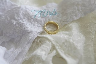 gold-wedding-band-on-top-of-lace-intimate-garments