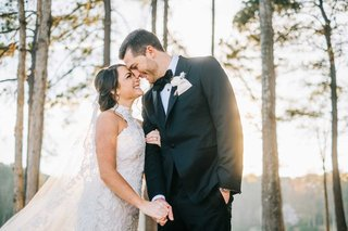 bride-in-high-neck-lace-wedding-dress-groom-in-suit-and-bow-tie-foreheads-touching-winter-portrait