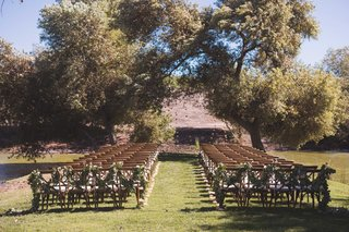 winery-wedding-wood-chairs-with-garlands-of-greenery-on-backs-winery-vineyard-outdoor-wedding