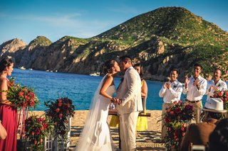 a-newlywed-couple-sharing-their-first-kiss-as-a-married-couple-on-a-beach-pacific-ocean-mexico