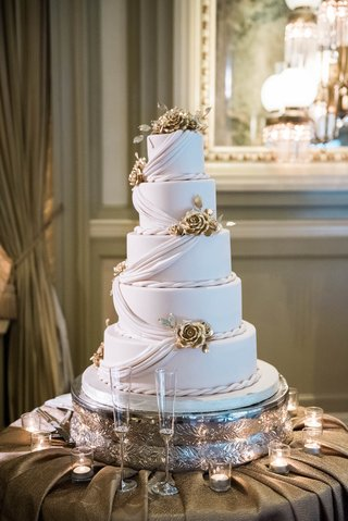 five-tiered-wedding-cake-with-fondant-drapery-and-rope-accents-with-golden-flowers