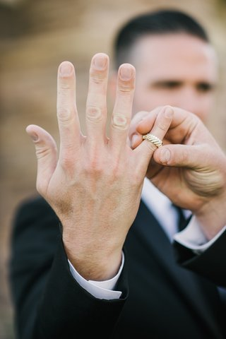 best-man-in-black-tuxedo-shows-the-grooms-yellow-gold-wedding-ring-and-brides-diamond-wedding-ring