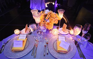 wedding-reception-table-with-silver-chargers-gold-napkins-yellow-roses-white-hydrangeas-candles