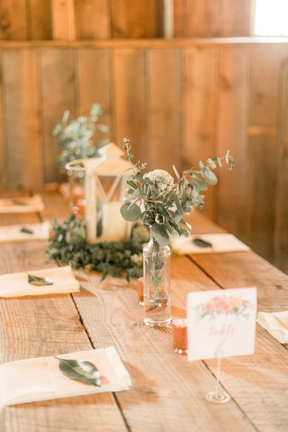 rustic-wedding-reception-low-diy-centerpieces-lantern-eucalyptus-greenery-napkin-green-leaf-escort