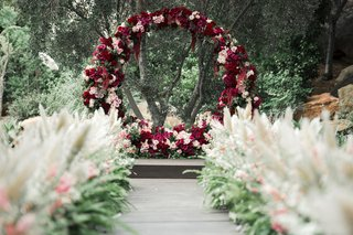 circle-ceremony-arch-made-with-marsala-and-blush-flowers-aisle-lined-with-pampas-grass