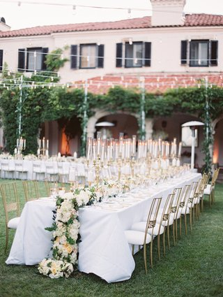 long-reception-tables-white-linens-gold-candelabra-cascading-floral-runner-gold-chairs