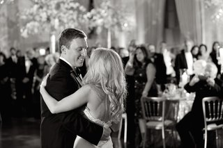 black-and-white-photo-of-groom-in-tuxedo-dancing-with-bride-in-a-strapless-dress