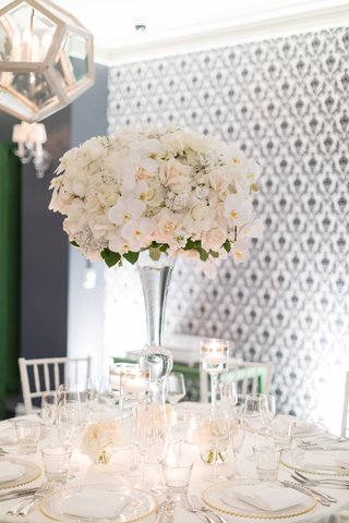 tall-glass-stand-with-white-orchids-and-ivory-roses-grey-patterned-wall-geometric-chandelier