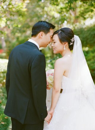 bride-with-updo-and-long-veil-holding-hands-with-groom