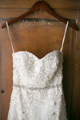 brides-wedding-dress-hanging-up-on-hanger-floral-details-mrs-williams