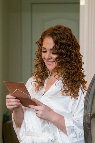 bride-with-curly-red-hair-reading-note-from-groom-before-wedding-in-white-satin-robe