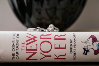 the-new-yorker-book-with-wedding-band-eternity-band-and-engagement-ring-on-top