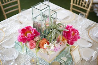 centerpiece-composed-of-square-vases-with-pink-and-orange-flowers-succulent-and-floating-candles