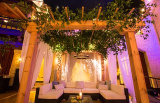 wedding-reception-lounge-area-wood-pergola-greenery-chandelier-sectional-with-coffee-table-candle