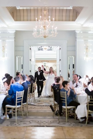 bride-and-groom-holding-hands-as-they-walk-into-ballroom-reception-at-casa-del-mar-guests-sitting