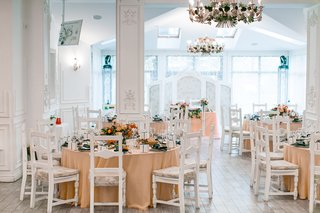 white-reception-space-colorful-tablescapes-champagne-colored-linens-round-tables-ukrainian-wedding