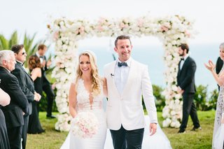 bride-and-groom-walking-up-aisle-outdoor-wedding-ceremony-guests-clapping-white-pink-flowers